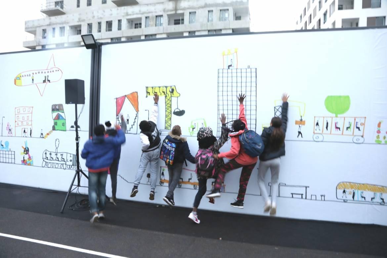 Les élèves du groupe scolaire Simone-Veil devant la fresque qu'ils ont contribué à réaliser dans la cour de l'école Simone-Veil de Villeurbanne.
