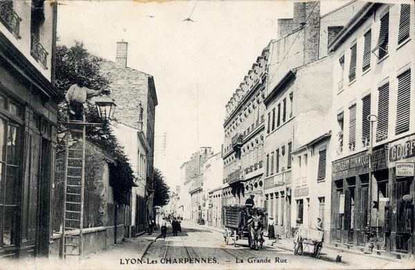 Grande Rue des Charpennes, le tramway électrique fonctionne déjà pour les voyageurs,  mais ce sont les voitures tirées par les chevaux qui approvisionnent encore commerces et ateliers.